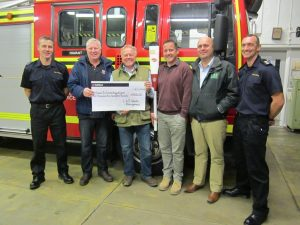 L&S team presenting cheque to the RNLI and Fire Fighters Charities.