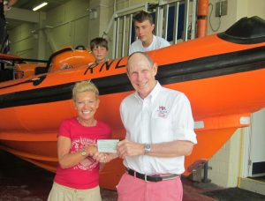 Jill Hughes handing over the cheque, watched by James and George Gilbert